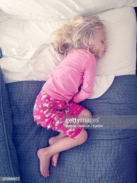 High Angle View Of Girl Sleeping On Bed