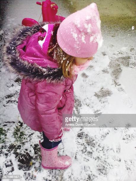 High Angle View Of Girl Standing On Snow Covered Field During Winter