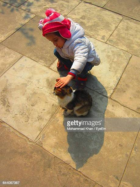 High Angle View Of Girl Stroking Cat On Paving Street