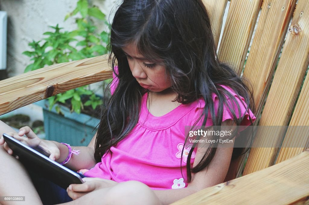 High Angle View Of Girl Using Digital Tablet On Chair In Back Yard