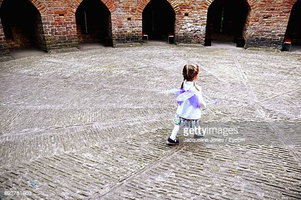 High Angle View Of Girl Walking With Purple Wings On Footpath