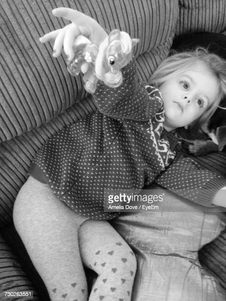 High Angle View Of Girl With Toy Relaxing On Sofa At Home