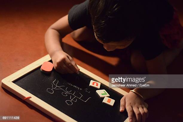 High Angle View Of Girl Writing On Slate While Sitting On Floor At Home