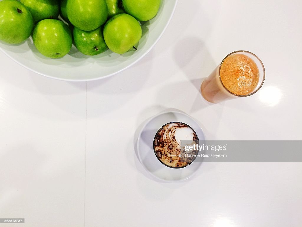 High Angle View Of Granny Smith Apples With Juice And Cappuccino Served On Table