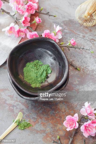 High Angle View Of Green Matcha Tea In Bowl Amidst Flowers