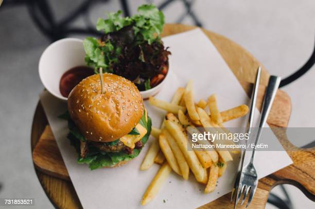 High Angle View Of Hamburger With French Fries Served In Plate At Restaurant