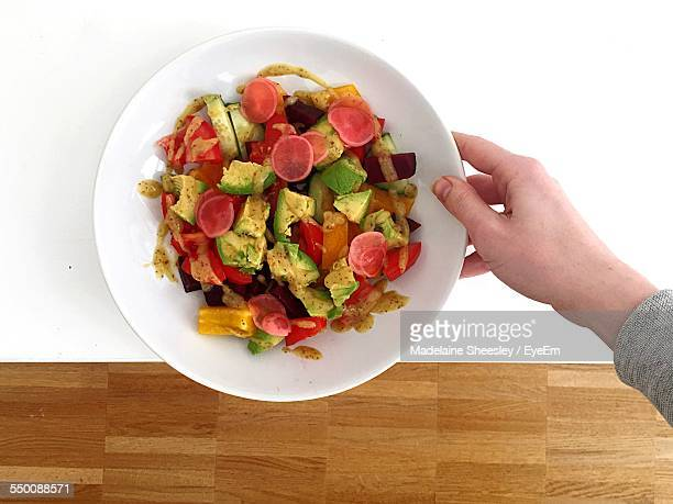 High Angle View Of Hand Holding Salad Bowl On Table