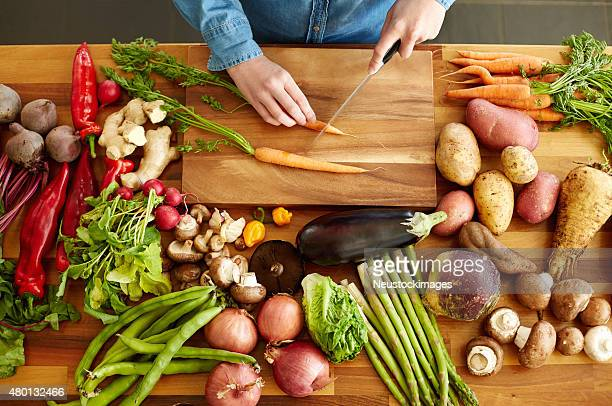 High angle view of hands cutting carrots by various vegetables