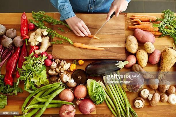の高角度のビューの手によって様々な野菜カティングニンジン