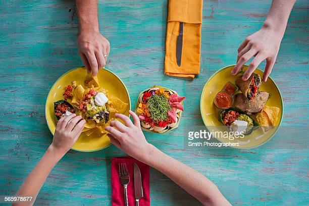 High angle view of hands reaching for food on plates