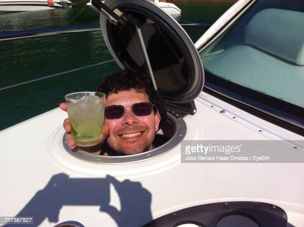 High Angle View Of Happy Man Holding Drink While Looking Through Boat Window