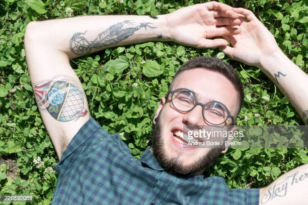 High Angle View Of Happy Tattooed Man Lying Down On Field During Sunny Day