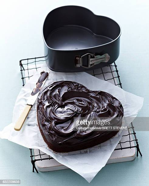 High angle view of heart shaped chocolate cake with chocolate ganache on cooling rack