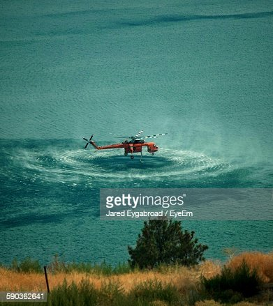 High Angle View Of Helicopter Hovering Over Sea