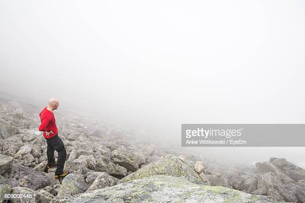 High Angle View Of Hiker Standing On Rocks During Foggy Weather