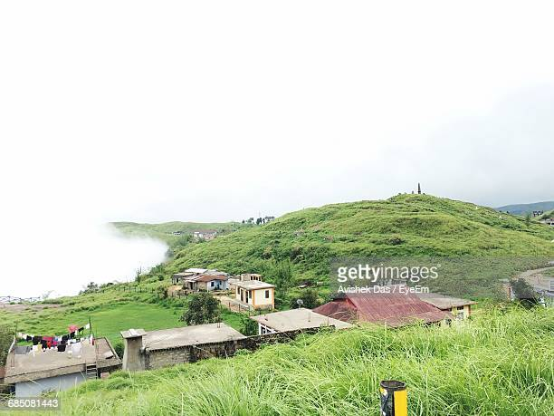 High Angle View Of Houses On Grassy Field In Foggy Weather