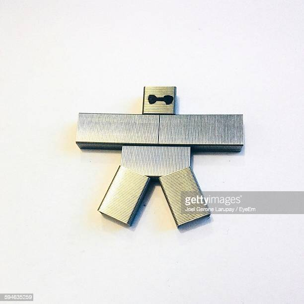 High Angle View Of Human Made From Stapler Pins Against White Background