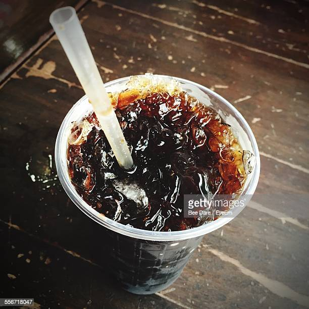 High Angle View Of Iced Coffee With Drinking Straw On Wooden Table
