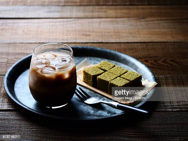 High Angle View Of Iced Coffee With Snack Served On Table