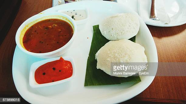 High Angle View Of Idli And Curry Served In Plate