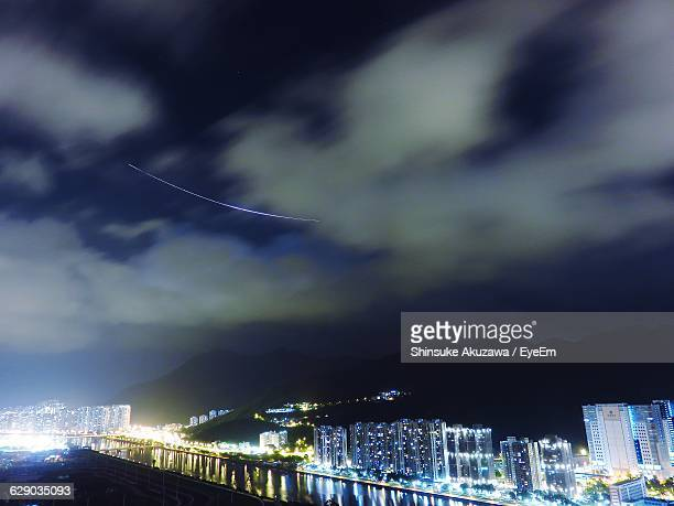 High Angle View Of Illuminated Cityscape Against Cloudy Sky At Night