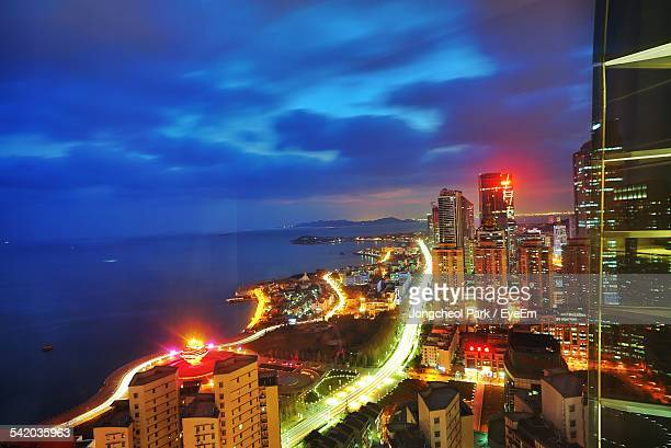 High Angle View Of Illuminated Cityscape By Sea Against Cloudy Sky