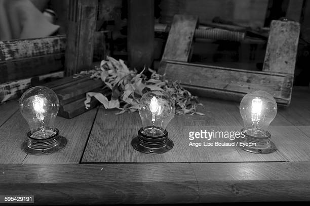 High Angle View Of Illuminated Light Bulb On Wooden Table