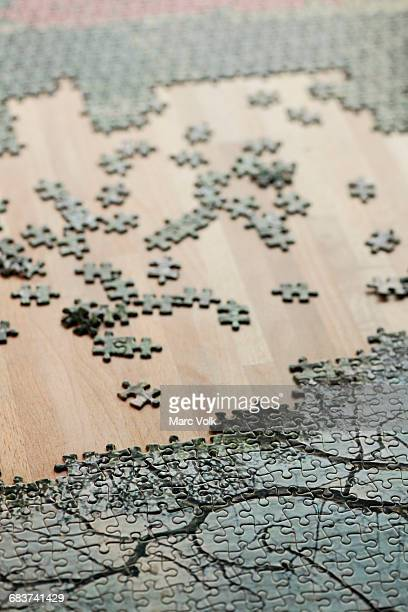 High angle view of jigsaw puzzle and pieces on wooden table