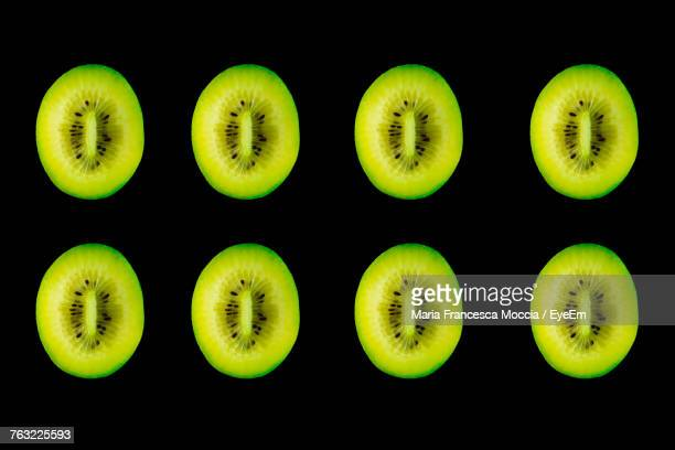 High Angle View Of Kiwi Slices Arranged On Black Background