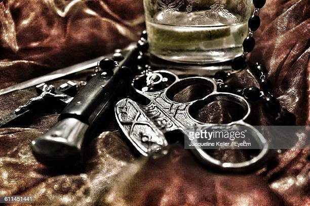 High Angle View Of Knife And Rosary With Knuckle On Table