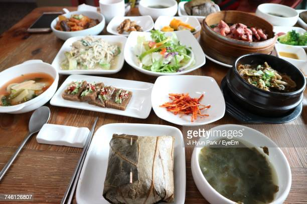 High Angle View Of Korean Food Served On Wooden Table