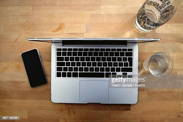 High Angle View Of Laptop With Glass And Mobile Phone At Desk