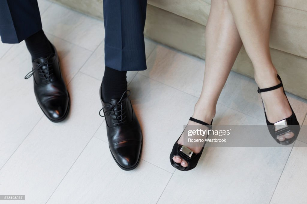 High angle view of legs of business people sitting on sofa