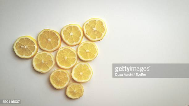 High Angle View Of Lemon Slices Arranged Over White Background