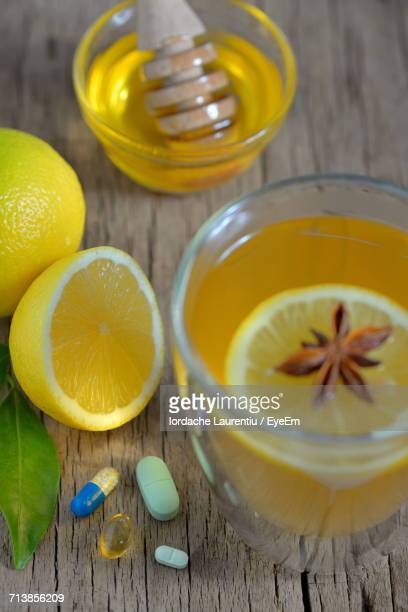 High Angle View Of Lemon Tea By Pills On Wooden Table