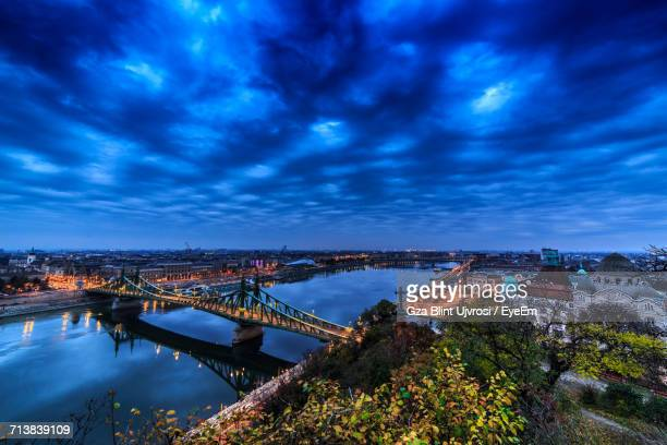 High Angle View Of Liberty Bridge Over Danube River Against Cloudy Sky In City At Dusk
