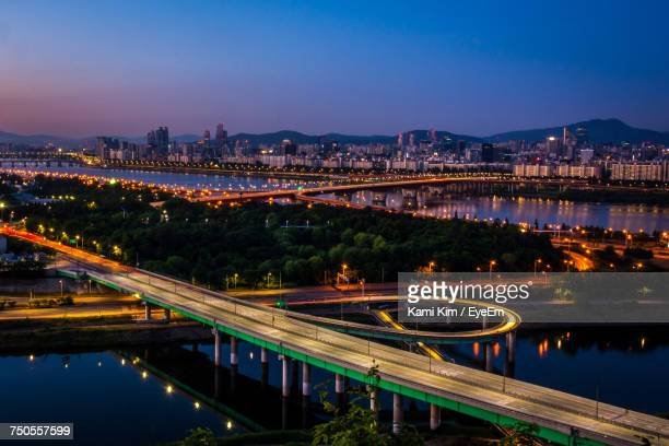 High Angle View Of Light Trails On Bridge Over River