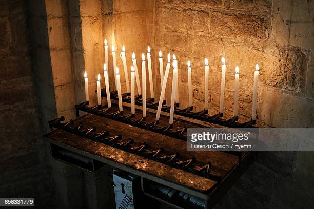 High Angle View Of Lit Candles On Altar In Church