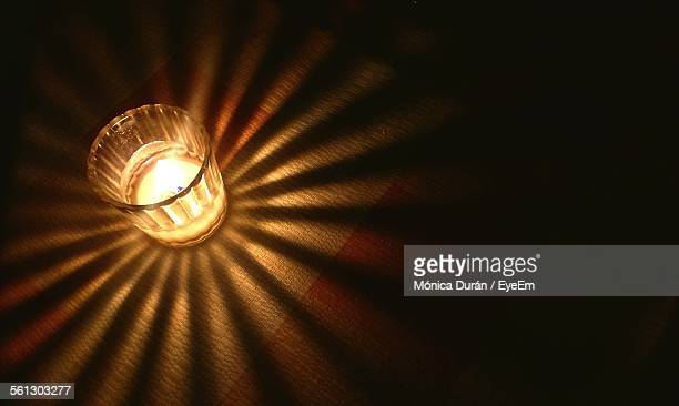 High Angle View Of Lit Tea Light Candle On Table In Darkroom