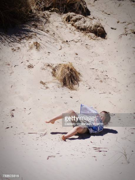 High Angle View Of Little Boy Lying At Beach On Sunny Day