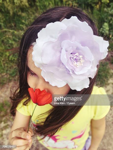 High Angle View Of Little Girl Wearing Headband While Smelling Poppy Flower