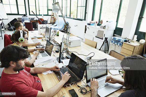 High angle view of male and female office workers typing on laptops in office
