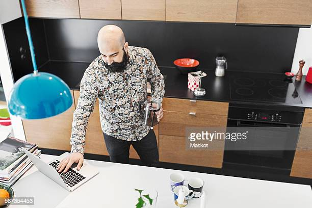 High angle view of male architect using laptop at counter in kitchen