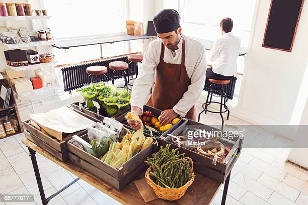 High angle view of male owner arranging vegetables at grocery store