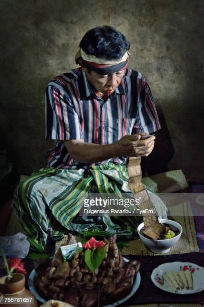 High Angle View Of Male Vendor Reading Text While Selling Food At Night