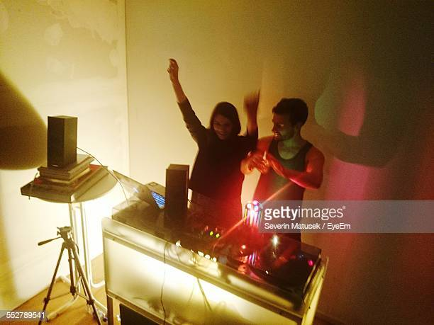 High Angle View Of Man And Woman Playing Music By Turntable At Nightclub