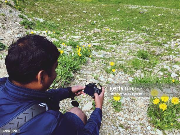 High Angle View Of Man Photographing Yellow Daisy With Camera On Field