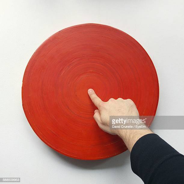 High Angle View Of Man Pointing At Red Circle Center Against White Background