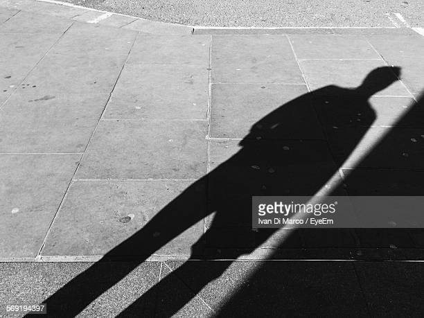High angle view of man shadow on footpath by Oxford Street