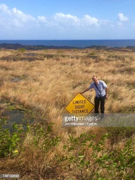 High Angle View Of Man Standing By Signboard Against Sky